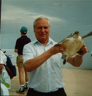 Picture of Annabel's Dad holding a turtle (on holiday in the Caymen Islands)